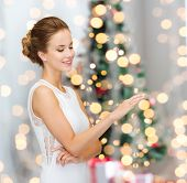winter holidays, presents and people concept - smiling woman in white dress wearing diamond ring over blue over christmas tree lights background