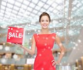 sale, christmas, holidays and people concept - smiling woman in red dress with sale sign over shopping center background