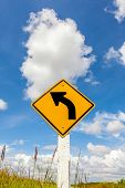 Curved Road Traffic Sign In Farmland With Cloudy Blue Sky Background.