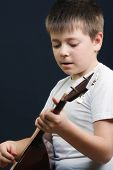 Boy In White Playing Balalaika