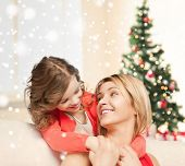 people, motherhood, family, christmas and adoption concept - happy mother and daughter hugging at home