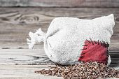 Concept of the thrift storing - Red rice in the burlap sack with the patch on a wooden background