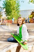 Smiling girl with skateboard sitting on playground