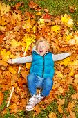 Boy laughing and laying on autumn leaves with rake