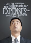 Businessman Looking Up In Word Cloud Of Expenses