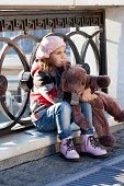 stock photo of beret  - Little girl in a pink beret holds a toy bear - JPG