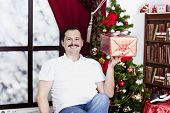 Happy Man With Gift Near A Christmas Tree