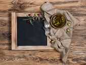 Top View Of Blackboard, Tableware And Olives With Olive Oil