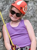 Smiling Young Girl Wearing Sunglasses And Climbing Equipment Inlcuding Helmet And Harness Waiting To