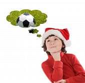 Adorable child with Christmas hat thinking with a soccer ball isolated on a white background