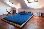 Interior, nice loft, bed with bedspread blue