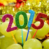 numbers of different colors forming the number 2015, as the new year, with a pile of grapes in the background