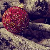 a red ornamented christmas ball on a pile of logs