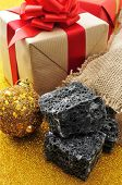 some lumps of candy coal and some christmas ornaments and gifts