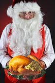 Santa Claus serving a fresh Roasted Thanksgiving or Christmas Turkey with all the trimmings. He is holding the platter in both hands in front of his torso. Vertical on a light to dark red background.