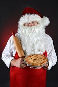 Santa Claus wearing a red apron and holding a fresh baked Apple Pie in one hand and a rolling pin in the other. Vertical format over a light to dark red background.