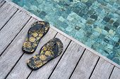 Black Floral Flip Flops of a Woman on Wooden Platform at the Edge of Clear Swimming Pool