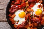 Fried Eggs With Chorizo In The Pan Close Up. Horizontal Top View