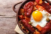 Eggs With Chorizo, Potatoes And Tomatoes In A Pot. Close Up Top View