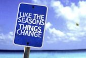 Like The Seasons Things Change sign with a beach on background