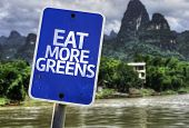 Eat More Greens sign with a forest background