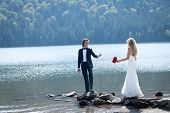 stock photo of daring  - Married couple having a relaxing and fun moment at the lake - JPG