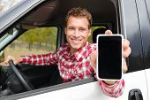 stock photo of driver  - Smartphone man driving car showing app on screen display smiling happy - JPG