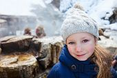 picture of macaque  - Little girl at Snow monkey Japanese Macaque park looking at monkeys bathe at onsen hot springs in Nagano - JPG