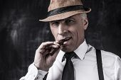 picture of suspenders  - Serious senior man in hat and suspenders smoking cigar and looking at you while standing against dark background - JPG