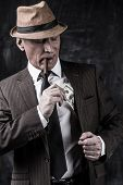 stock photo of suspenders  - Serious senior man in hat and suspenders smoking cigar and hiding money into the pocket while standing against dark background - JPG