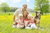 stock photo of shepherds  - Portrait of a happy family of four people including mother father young child and baby sitting outside with their German Shepherd mix dog on a Spring day - JPG
