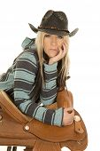 stock photo of western saddle  - a woman with a serious expression on her face looking stratight a head leaning on her saddle - JPG