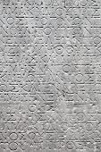 foto of chisel  - ancient Greek writing chiseled on stone texture - JPG