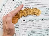 pic of irs  - Caucasian hand protecting wealth in solid gold eagle coins on USA tax form 1040 for year 2014 illustrating keeping assets away from the IRS - JPG