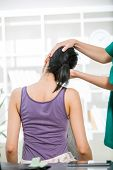 image of chiropractor  - Chiropractor adjusting neck muscles on female patient - JPG
