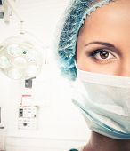 stock photo of mask  - Young woman doctor in cap and face mask in surgery room interior - JPG