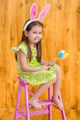 image of barefoot  - Barefooted little girl with long blond hair wearing pink white rabbit or bunny ears and holding bunch of colorful eggs sitting on pink chair - JPG