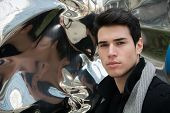 image of deformed  - Headshot of handsome young man next to deforming mirror looking at camera - JPG