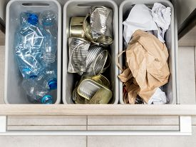 stock photo of segregation  - Three plastic trash bins in kitchen cabinet with segregated household garbage  - JPG