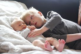 stock photo of laying-in-bed  - A big brother is lovinly hugging his newborn baby sister as they lay in bed together - JPG