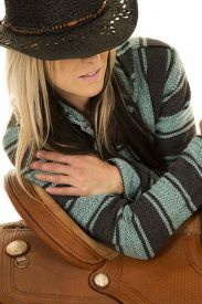 picture of western saddle  - A cowgirl in her western hat leaning against her saddle - JPG