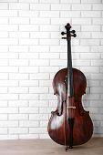 picture of cello  - Cello on bricks wall background - JPG