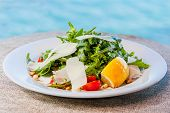 foto of pine nut  - Salad with arugula cherry tomatoes pine nuts parmesan cheese - JPG