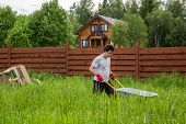 picture of hand-barrow  - man carries a wheelbarrow through a thicket of grass