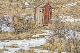 stock photo of outhouse  - Outhouse with rusty hinges and rusty metal on the side in a Montana ghost town - JPG