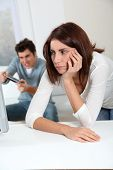Young woman fed up with boyfriend playing video game