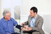 Doctor taking old man's blood pressure