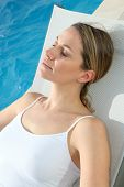 Woman relaxing in deckchair by swimming-pool
