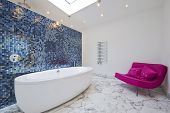 large modern porcelain bath and a magenta pink sofa