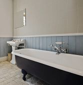 classic bathroom with glazed alloy bath tub and vintage shower attachment